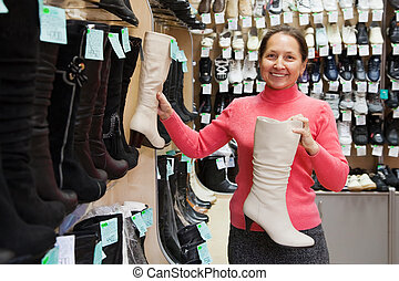 Mature woman chooses wintry shoes at shoes shop