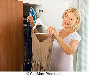 Mature woman choosing dress at home