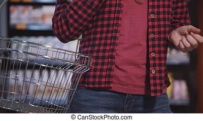 Mature woman choosing fresh products in the hypermarket -...