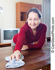 Mature woman cleaning wooden table with rag