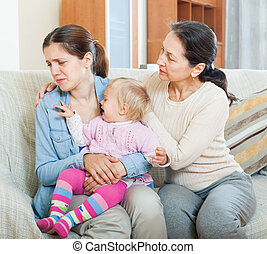 Mature woman comforting adult daughter with toddler