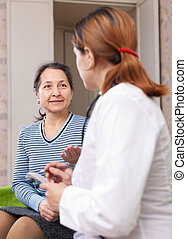 mature woman complaining to doctor about symptoms. Focus on ...
