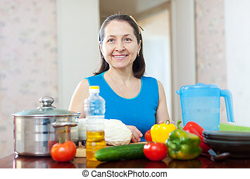 mature woman cooking lunch
