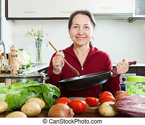 mature woman cooking with skillet in domestic kitchen