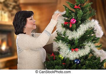 Mature woman decorating Xmas tree