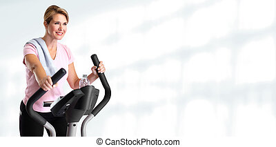 Mature woman doing exercise on elliptical trainer. - Mature...
