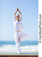 mature woman doing yoga exercise - fit mature woman doing...