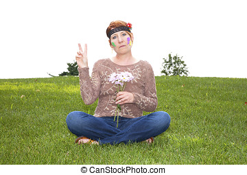Mature woman dressed as a sixties flower child sitting in the grass holding daisies and flashing a peace sign
