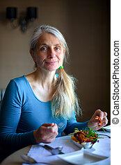 Mature woman enjoying a calamari starter