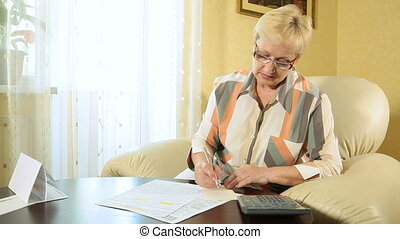 Mature woman filling out tax form