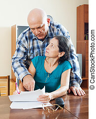 mature woman fills documents,  man helping her