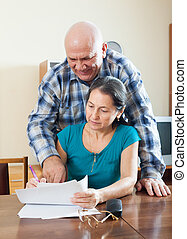 Mature woman fills documents,  man helps her