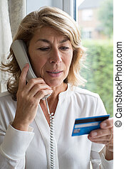 Mature Woman Giving Credit Card Details On The Phone