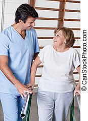 Mature Woman having ambulatory therapy - Mature man having...