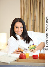 mature woman having breakfast and relaxing on the sofa