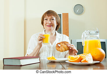 mature woman having breakfast with juice