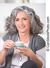 mature woman having cup of coffee home