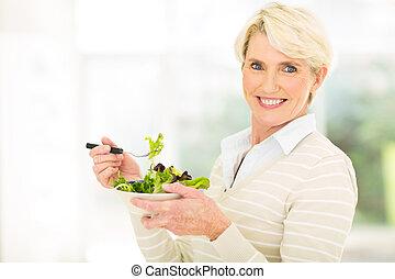 mature woman having green salad