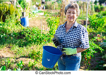 Mature woman having horticultural instruments in garden on day