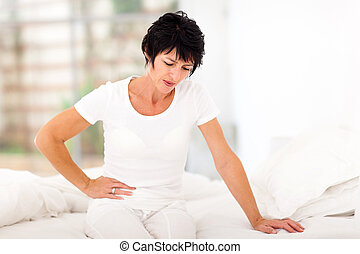 mature woman having stomach ache - mature woman sitting on...