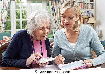 Mature Woman Helping Senior Neighbor With Home Finances