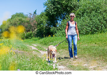 mature woman hiking with dog in the landscape