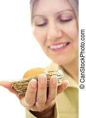 Mature woman holding a nest with an egg