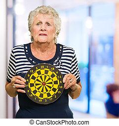 Mature Woman Holding Dart Board