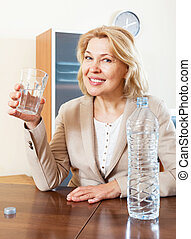 mature  woman holding glass filled with water
