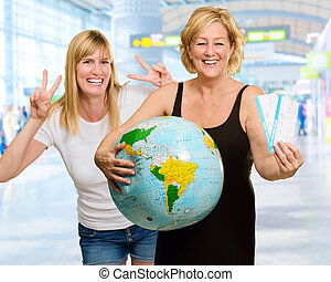 Mature Woman Holding Globe In Front Of Happy Young Woman