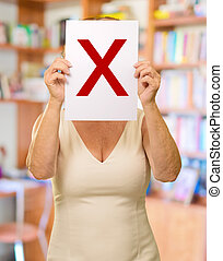 mature woman holding Letter X sign board