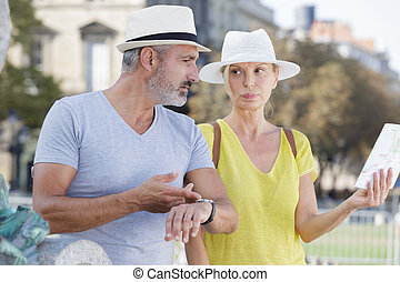 mature woman holding map man stressing the time restrictions