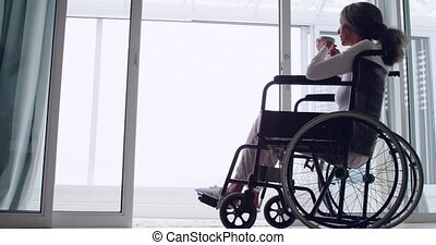 Mature woman in a wheelchair - Side view of a mature mixed...