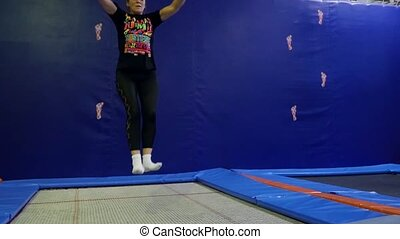 Mature woman in aged jumping on trampoline in sport centre...