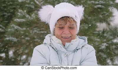 Mature woman in aged throwing snowflakes in slow motion in the park in winter has a fun.