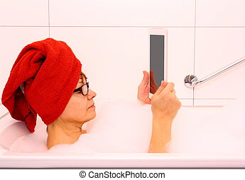 Mature woman in bathtub with tablet