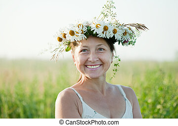 mature woman in camomile wreath - Outdoor portrait of mature...