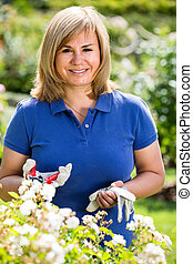 mature woman in garden on summer day.