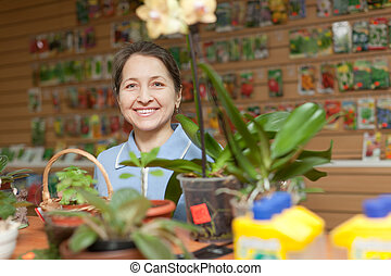 mature woman in garden shop - mature woman looks flower in...