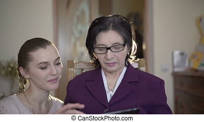 Mature woman in glasses sitting, using the tablet, girl coming to her in a room