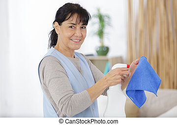 mature woman in protective gloves is smiling and wiping dust