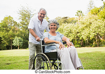 Mature woman in wheelchair with partner smiling at camera at...