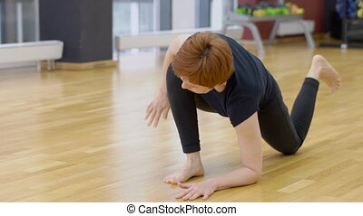 Mature woman is having yoga training in modern gym, slow motion.