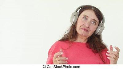 Mature woman listening music wireless headphones