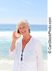 Mature woman listening to her shell