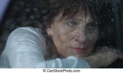 Mature woman look at rain through the window - Melancholy...