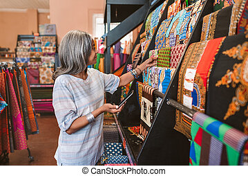 Mature woman looking at colorful fabric in her shop