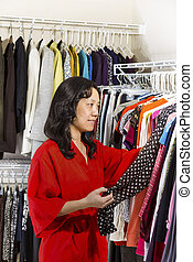 Mature woman looking at Dress Top in Morning
