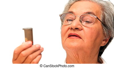 Mature woman looking at her pills