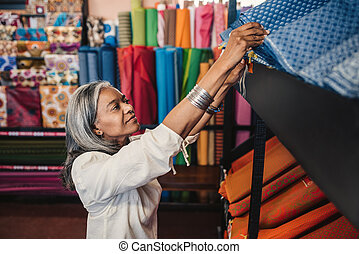 Mature woman looking through cloth rolls in a fabric shop